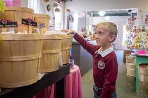 "Little boy thinking, ""Really, I can take a whole handful of candy from this basket?"" at Sugar Momma's"