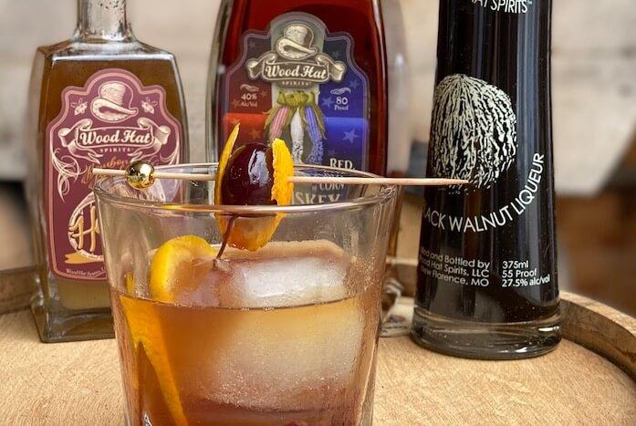 honey black walnut old fashioned with whiskey bottles in background